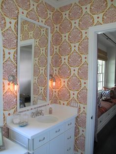 Amber Interiors: Sweet girl's bathroom with pink & orange wallpaper and white bathroom vanity.