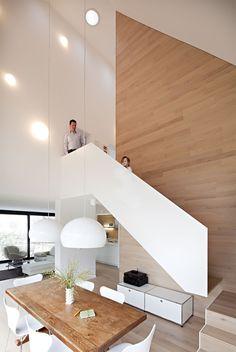 Aufstieg: Ebenso wie die Wand ist die neue Treppe mit gekalktem Eichenholz belegt, das weiße Geländer macht sie zur Skulptur. Auch Küche und Sitzmöbel sind in der hellen Farbe gehalten – schlicht und klassisch.