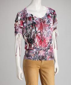 Fresh and trendy with a sublimation print, this terrific top is a fashionable look all on its own. The blouson silhouette is fitted at the hem, allowing the upper half to billow gently, while drawstring ties at each sleeve customize the look.