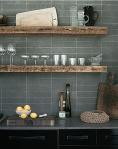 I love the reclaimed wood shelves in this contemporary kitchen. They're offset beautifully by the grey tiles.