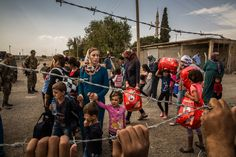 Kurdish women and children from Syria at a Turkish military checkpoint near Kobani, a Syrian town badly damaged by the war last year. Bryan Denton for The New York Times
