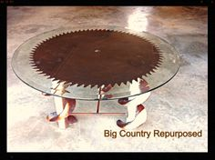 """I love old saw blades! Nothing says rustic industrial like this antique solid tooth sawmill blade I recovered. This table is supported with metal auger legs and I had a piece welded between the three legs for added support. The glass is 36"""" diameter with beveled edge. What a conversation piece! See more repurposed items on my FB page at Big Country Repurposed Furniture."""