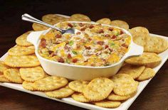 Creamy Bacon and Cheese Dip 16 ounces sour cream  8 ounces cream cheese, softened  2 cups (8 oz.) shredded Cheddar cheese  1 jar (3 ounces) bacon bits  1 cup chopped green onions  1 envelope onion soup mix  crackers  Assorted fresh vegetables (optional)   1. Oven - 400°F. In a mixing bowl, stir together sour cream and cream cheese. Fold in shredded cheese, bacon bits, green onions and onion soup mix.   2. Pour into 2-quart baking dish. Cover 7 bake for 25-30 min or til hot & bubbly.