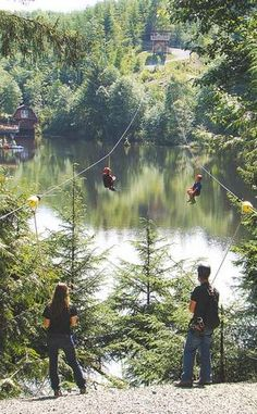 Two young brothers race across dual zip lines above a seven-acre pond at High Life Adventures near Astoria. Guides wait to assist their landing at the end of the quarter-mile glide.