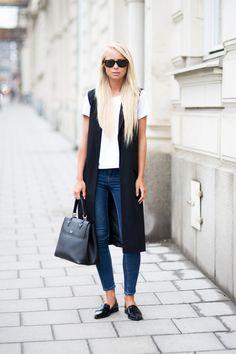 Colete preto alongado, t-shirt branca, bolsa preta, mocassim preto, jeans skinny, ócuilos de sol preto