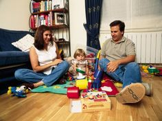 Parents sit with daughter as she plays with her toys.  Spain