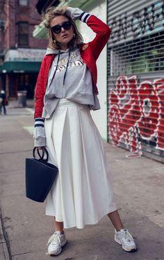 Rebecca Laurey combina saia jeans com moletom e tênis.