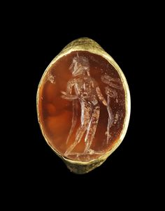 Golden ring with a ringstone made of orange cornelian showing a standing Mercury with kerykeion. Roman, 2nd - 3rd century A.D.
