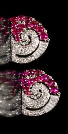 An art deco ruby and diamond double clip brooch, circa 1935 Of scrolling design, set with cabochon rubies and brilliant and baguette-cut diamonds, mounted in platinum, diamonds approximately 2.95 carats total, length 5.4cm