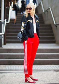 Alexandra Spencer wears an embroidered jacket + red track pants + red heels