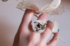 "On this pearl white button, I painted a raceme inspired by the tail of a peacock, although I chose my beloved gold, turquoise and black to represent it, colors I also picked up in small punctate decorations and in the leaves. It is a refined and elegant ring (like the animal which I was inspired by) and, at the same time, unusual. The ring's setting, silvery, is adjustable.   SPECS  * Button size: 0,98"" diameter  * Materials: I use only nickel free metal elements.  * I painted these jewels…"