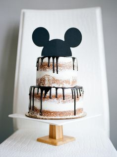 naked cake with Mickey ears cake topper // modern Mickey Mouse birthday party // acrylic white and wood modern cake stand // kid's birthday party inspiration // 2nd birthday party ideas // Blogger Lindsey Lutz from Life Lutzurious details her son Asher's Modern Mickey 2nd Birthday Party