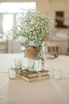 Simple, rustic centerpiece using old books, mason jar vases, Baby's Breath, and candles from our wedding. Copyright - Jerdan Photography