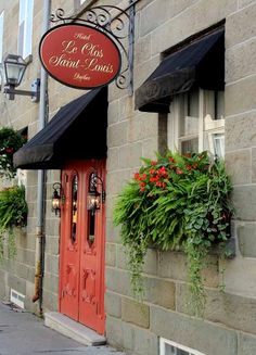 Coral door in Quebec City. I love the black awnings with the coral door and the window box plantings.