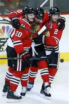 Chicago Blackhawks left wing Brandon Saad (20), left wing Patrick Sharp, center, and defenseman Duncan Keith (2) celebrate after Sharp scored a goal against the San Jose Sharks during the second period of an NHL hockey game on Sunday, Nov. 17, 2013, in Chicago. (AP Photo/Andrew A. Nelles)