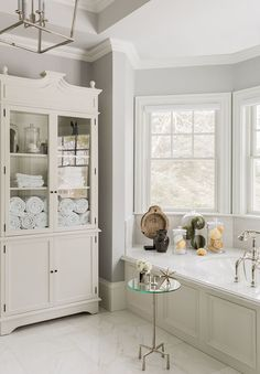 Dreamy neutral master bathroom! Such a smart way to store towels and toiletries in this glass door chest Hudson Interior Designs