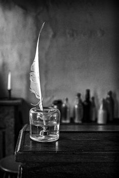 Black and white photograph of desk with quill pen by Jeff Burton