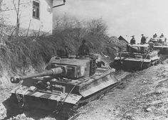A column of Tiger 1 tanks passing through a rural village area