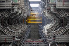 A heavy-lift crane lifts the first half of the F-level work platforms, F south, for NASA's Space Launch System (SLS) rocket, into position for installation in High Bay 3 of…