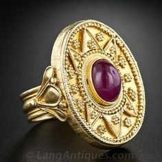 Lalaounis 18K Cabochon Ruby Ring. From the Grecian Isles comes this bold and fabulous ancient-style bauble designed and crafted in rich 18 karat yellow gold and featuring a 2.00 carat cabochon ruby by the noted jeweler Lalaounis. The sizable (1 by 3/4 inch) ring is ornamented throughout with tiny granulated bead work, hand engraving, a fluted ring shank and a hand hammered finish underneath.