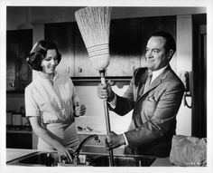 Lana Turner watches Bob Hope handle a broom in a scene from the film 'Bachelor In Paradise' 1961