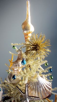 Create a tree topper by removing the cap from a shell ornament! Featured on Beach Bliss Living: http://beachblissliving.com/mini-beach-christmas-trees/