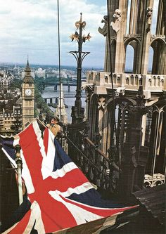 Preparations being made to fly the Union Flag from the flagpole atop Victoria Tower, Palace of Westminster. This is 1946 and the camera has caught a glimpse of one of the three emergency bridges thrown across the Thames during WW2.