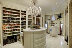 Feminine luxury walk in closet with beautiful chandelier island and makeup counter