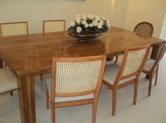 Mesa de jantar em madeira de demolição com arranjo floral...