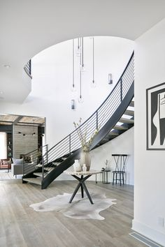 A Modern, Industrial, and Family-First Home- Black modern curved staircase with a double ceiling height and glass orbs chandelier + cowhide rug and a round table in the entryway Double Staircase, Entryway Stairs, Staircase Railings, Staircase Design, Entryway Decor, Entryway Ideas, Entryway Round Table, Staircase Runner, Staircase Ideas