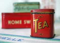 bright red tea canister or tin with TEA in angled gold letters on rectangular shape with rounded corners, friction cap lid, mid 20th century