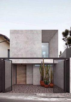 A fachada de cimento queimado fica completamente exposta graças ao uso da grade vazada quadriculada