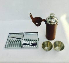 Set flask drink, stainless steel brown leather with two integrated cups and a stainless steel cigarette holder, cigarette case, snuffbox, excellent as a gift for a man or gift.  The two objects are marked in stainless steel and in good vintage conditions.  With this stainless steel and leather flange, you will travel to the highlands of Scotland, where the best whiskeys in the world are made. You will be able to discover this beautiful object all in stainless and protected by a leather case…