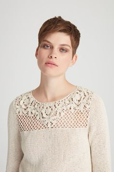 This sweater features bracelet-length sleeves and a floral panel. 100% cotton, hand knitted in Nepal.