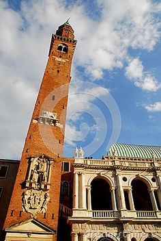 Photo taken at the Palladian Basilica in Vicenza in Veneto (Italy). In the image, taken from the Piazza dei Signori, you see, in the foreground, the slender bell tower with bas-reliefs that penetrates into the blue sky speckled with white clouds. Behind the bell tower you can see a part of the great historic and beautiful building façade illuminated by the sun as the bell tower.