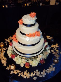 White 4 tier wedding cake with royal blue trimming and peach flower decoration.