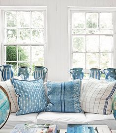 Patterned blue, denim and white pillows on couch with white slipcover for easy cleaning.