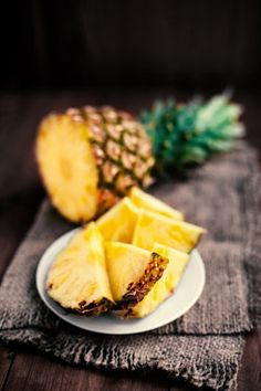 Pineapple tropical fruit / Ananas with slices over wooden table - stock photo