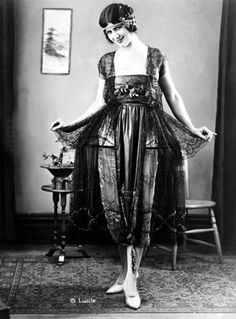 Woman modeling evening gown by Lucile, with a black chantilly hoop skirt over white satin, at the National Retail Garment Association Fashion Show at the Hotel Commodore, New York City. 1921