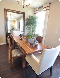 A very cool rustic dining room table, and a great mix of non matching armchairs and side chairs. The oversized mirror helps expand the space.
