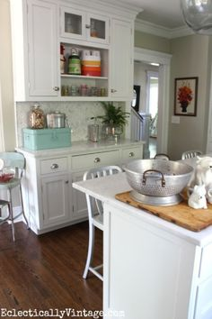 Love this bright white kitchen! See how easy it is to change the look of your kitchen with some fun accessories like the brightly colored aqua metal box from HomeGoods that holds barbecue necessities EclecticallyVintage.com sponsored pin