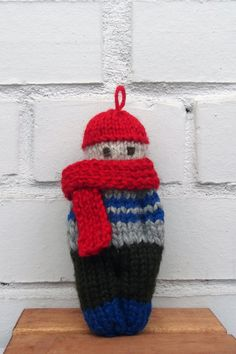 """Meet """"the little introverts""""! I knit them using woolen and acrylic yarn in a smoke free home. They are not talkative, but have their own personality and attitude. One of them could be your friend. Each doll is stuffed with sintepon, eyes are embroidered.  This little boy is wearing a grey sweater with a blue stripes, red hat and a big scarf. Scarf can be detachable. He is 7x16 cm (2,7x6,3 in) in size and ready to ship! Feel free to ask me, if you have any questions. Mako"""