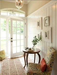 White wood  paneling,  frames, and   side chair create a cozy cottage .