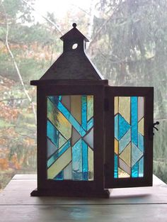 An abstract design on a rustic wood lantern would be just the thing to brighten up your table either outside or inside! Also, makes a great light in an entryway. 5 inches wide and 14 tall to the tip of the cap. This lantern can be lit in various ways from a string of mini lights or a