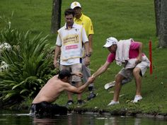 MALAYSIA / April 18, 2014 Pablo Larrazabal, left, of Spain, is pulled out of a lake after being attacked by a swarm of hornets during the second round of the Malaysian Open golf tournament at Kuala Lumpur Golf and Country Club in Kuala Lumpur, Malaysia, Friday, April 18, 2014.