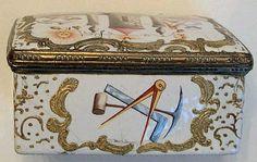 Boite en émail de forme rectangulaire. Son couvercle est peint d'une tour représentant le Temple. Sur les cotés, les deux colonnes et les outils symboliques, compas, équerre, niveau, truelle, soleil et lune. Les autres sont aussi ornées de nombreux symboles: truelle, compas, maillet, temple, pioche, niveau, équerre... Vraisemblablement une réalisation de la manufacture de Battersea (Londres) vers 1780. Vente aux #encheres du 02/03/13 par Cannes Enchères