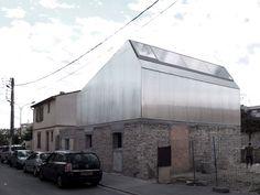 Dans ce paysage de faubourg toulousain, cette construction réinterprète la typologie à pignons sur rue caractéristique de la rue de la Briqueterie. En contraste avec le socle maçonné conservé dont la texture est volontairement mise en valeur par un bad...
