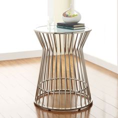205 Keep your favorite book or beverage close at-hand with this glass-top chrome accent table. Featuring an open base design, this side table will provide an element of visual interest in any modern decor. A nickel finish offers a sophisticated touch.