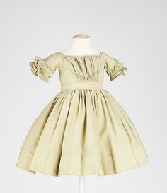 1845–50, American, wool, cotton: Length at CB: 18 in. This is a very high-styled, hand-sewn infant's dress mimicking the fashionable 1840s V-shaped gather bodice configuration from center front shirring. It is finely finished in all aspects including the well-sewn integral lining, the self ruffles with binding at the edges, and the fine piping around the neck. The lightweight sheer wool of the dress is known as albatross, so named because it is soft as the underbelly of the albatross.