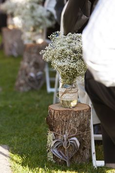 Rustic Wedding Ceremony - Aisle - DIY wood stumps with paper hearts tied with jute, mason jars decorated with crochet lace and jute, filled with babys breath and lavender  Photo c/o Janell Aitken Photography